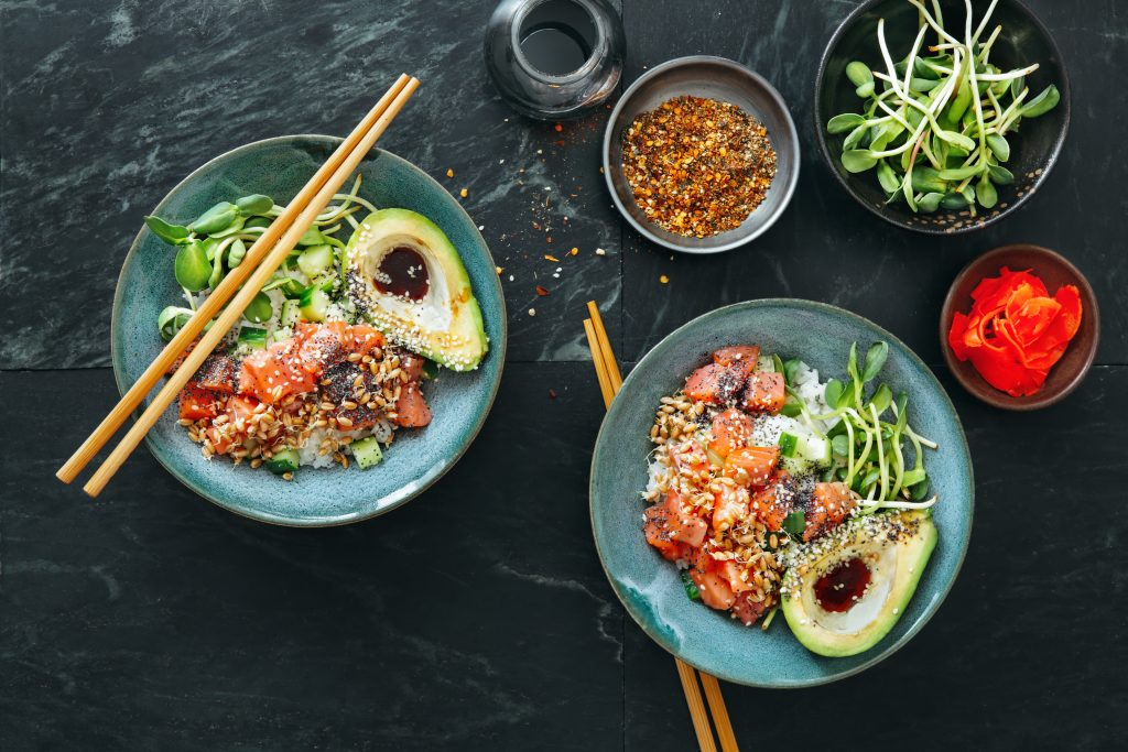 Poke bowls with salmon, avocado, vegetables, sprouts and ponzu dressing on marble background